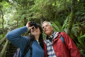 Middle Aged Couple With Binoculars In Forest